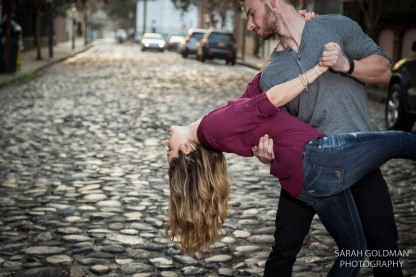 engaged couple dips on a cobblestone street in charleston
