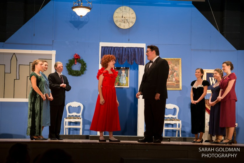 annie and daddy warbucks talking on stage