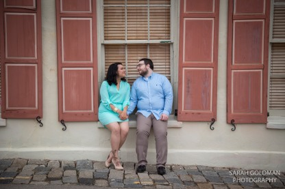 engaged couple sitting on window ledge in charleston