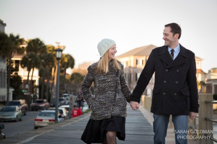 engaged couple in charleston walking on the battery wall