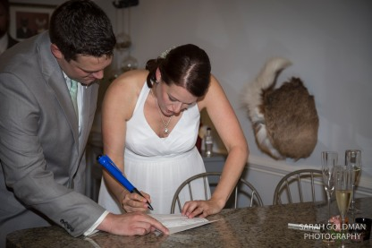 bride and groom signing the marriage license