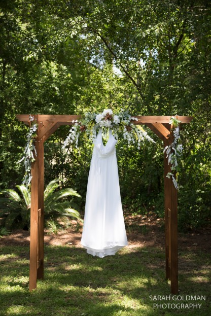brides dress hanging from arbor