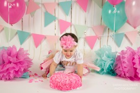 little girl with pink cake during cake smash session