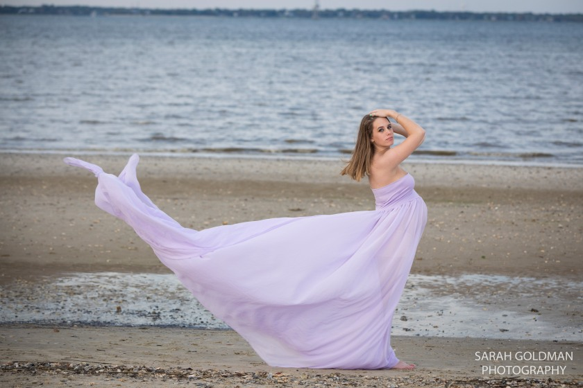 model in purple maternity gown on the beach