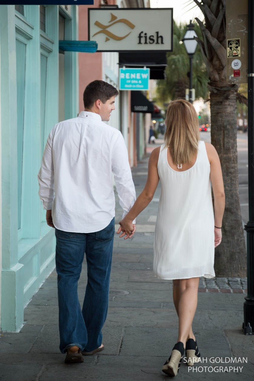 engaged couple walking down king street in charleston