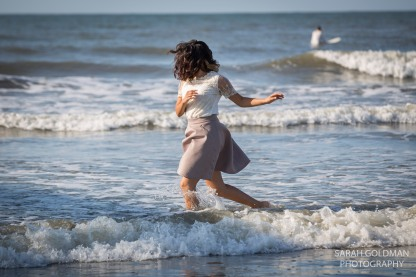 girl running in the ocean at folly