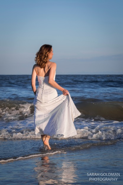 bride wading into ocean at folly beach