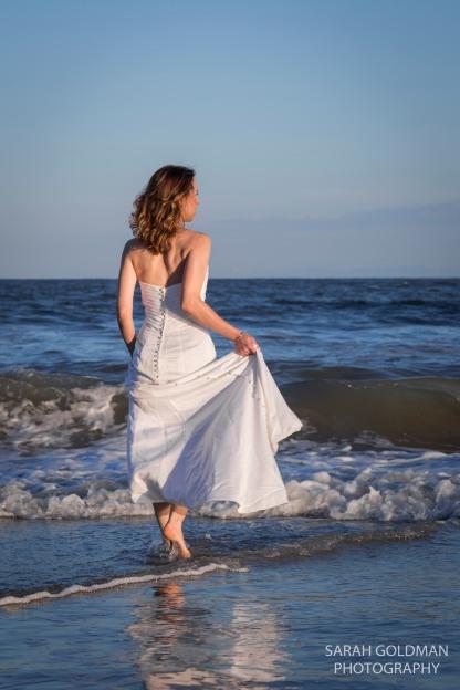 bride wading into ocean at folly beach