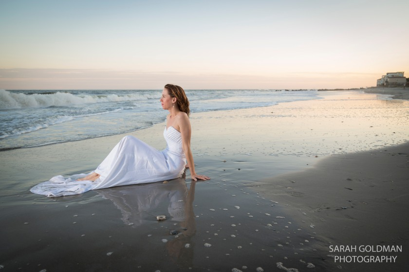 woman sitting on the beach in her wedding dress