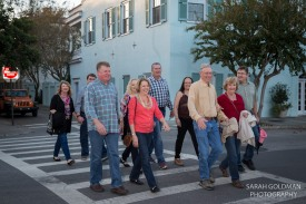 family walking across street near Rainbow Row