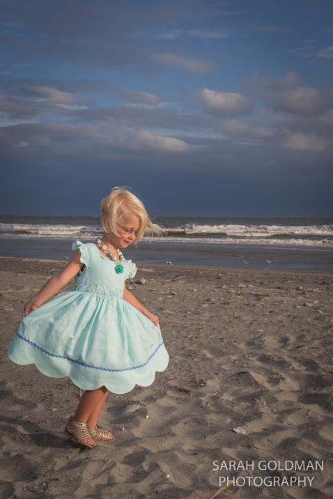 little girl in a dress at the beach