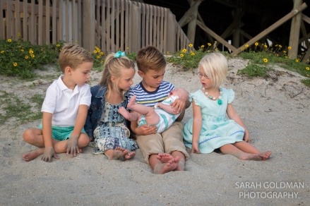 kids with new baby cousin near sand dunes