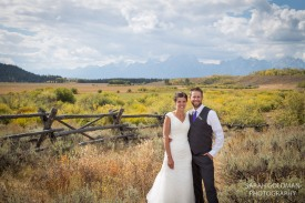 bride and groom with fence and grand tetons in background