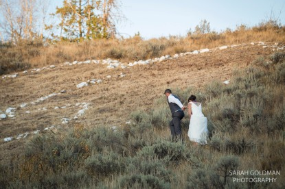 bride and groom climbing hill