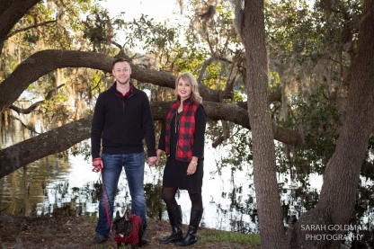 husband and wife by lake with live oaks