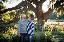 husband and wife looking at each other under a live oak