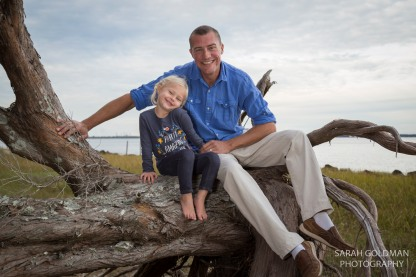 father and daughter sitting on driftwood on james island