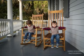 kids sitting in rocking chairs on the porch