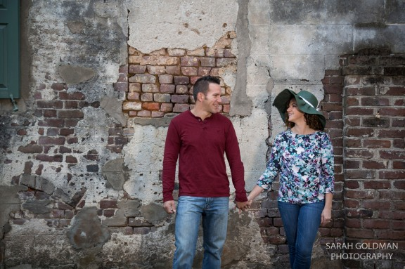 engaged couple holding hands in front of old wall