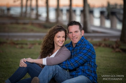 couple sitting on ground in waterfront park