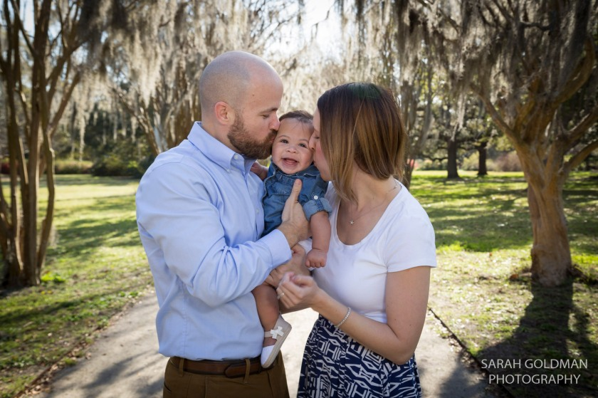 mom and dad kissing baby with spanish moss in background
