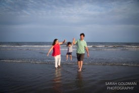family playing at the beach iop