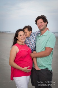 young family on the beach with pregnant mom