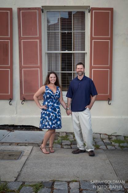 couple holding hands near Rainbow Row