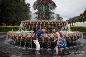 couple playing in fountain in waterfront park