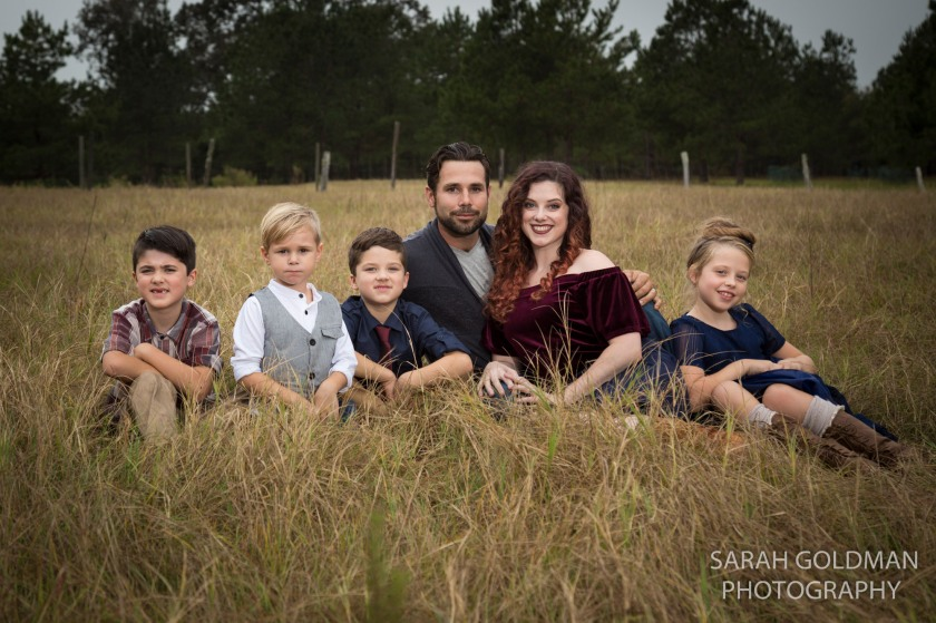 family sitting in a field in the country in south carolina