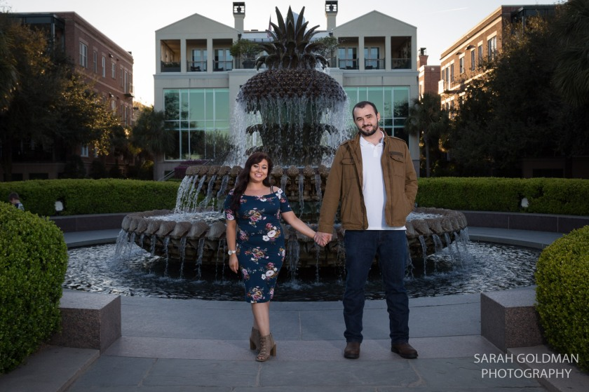 Engaged couple standing in front of Pineapple Fountain